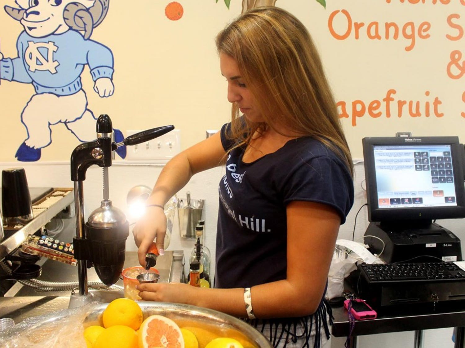 Sup Dogs on Franklin Street opened Monday morning. Waitresses work on the signature orange crush behind a full bar inside the restaurant.
