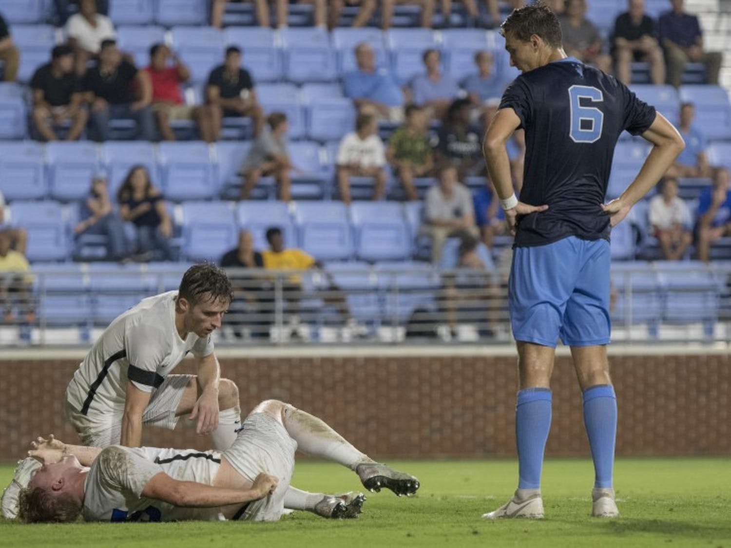 UNC junior Matt Constant (6) looks on at an injured Duke player that was later taken off by an ambulance.