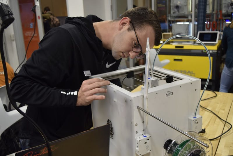 Program Assistant Michael Aruch, a senior economics major, performs maintenance on a dysfunctional 3D printer in the Kenan Science Library Makerspace Wednesday, Nov. 14, 2018.