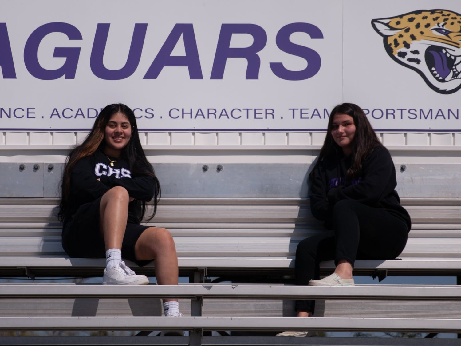 Carrboro High School sophomores Fabiola Perdomo and Sofia Rangel sit in the Carrboro High football stadium. Perdomo and Rangel, like many young people from non-English speaking families, have had to guide their families through participating in school transitions and other difficulties that stem from the pandemic.