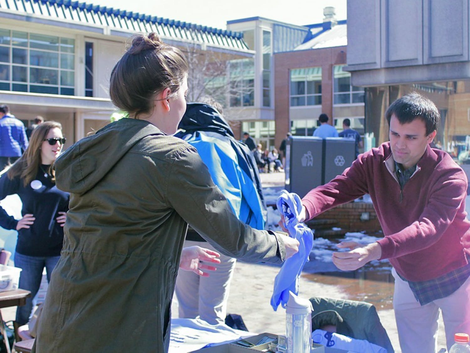 Chris Welch, public policy major, helps the Carolina Athletic association kickstart Beat Duke Week by selling Beat Duke shirts in the pit on Monday.