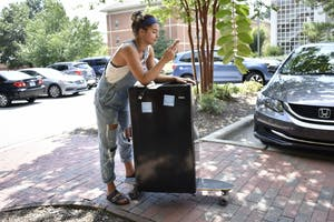 First-year Maddie Cagle, waits for her boyfriend to help her move her refrigerator from Craige residence hall to Craige North residence hall.