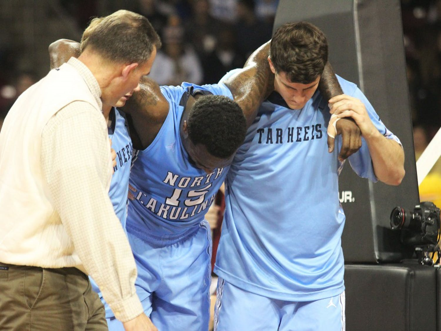 Hairston is helped off the court by his teammates and medical personnel.