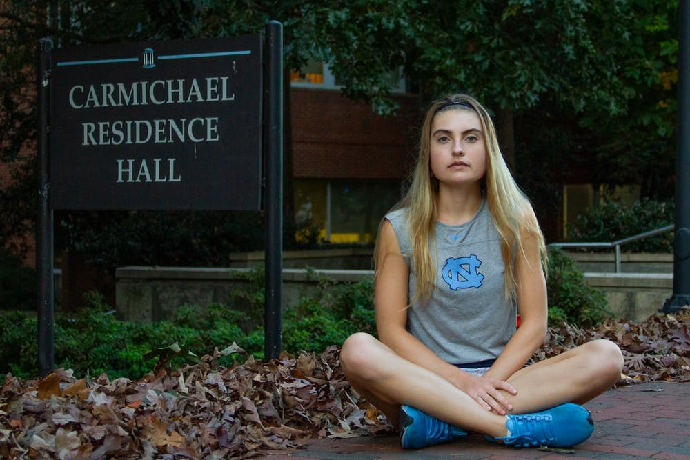 <p>Fiona Crawley, a first-year on the UNC Women's Tennis team, sits in front of her residence hall after getting back from tennis practice on Monday, Oct. 26, 2020.</p>