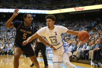 UNC guard Cam Johnson (13) fights past Notre Dame's D.J. Harvey (5) during game on Tuesday, Jan. 15 at the Smith Center. UNC won 75-69.