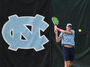 Blaine Boyden serving in UNC tennis match against Duke.