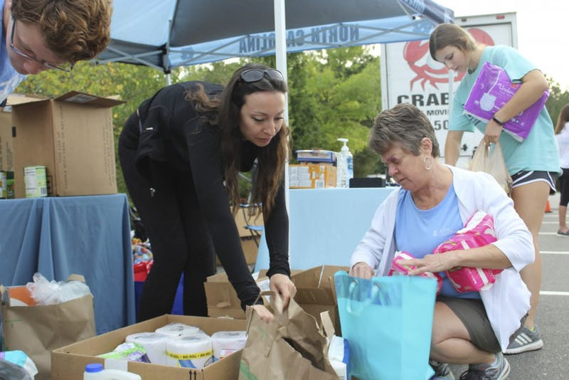 "(From left to right) Jed Higdon, Luisa Brooks, Michele Fulton and Jessica Bevard sort donated items at the ""Fill the Truck"" relief drive for Hurricane Florence early Tuesday morning on Oct. 9, 2018."