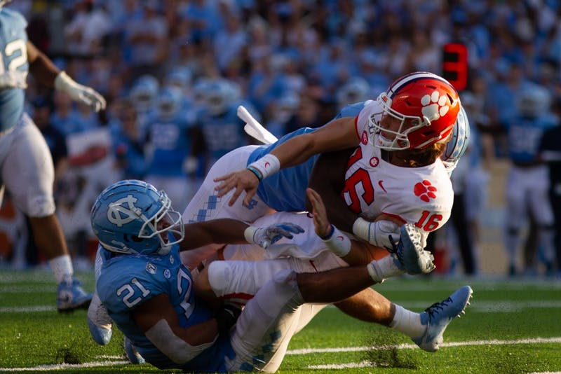 Clemson quarterback Trevor Larwrence (16) is knocked down by UNC linebackers Chazz Surratt (21) and Tomon Fox (12) during the football game on Saturday, Sept. 28th, 2019 at Kenan Memorial Stadium. UNC lost to Clemson 21-20.