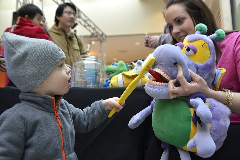 Kidzu Children's Museum partnered with Southern Village Pediatric Dentistry for an event on Saturday morning. Raphael Glassman, 18 months, practices his brushing on a stuffed dinosaur at the event.