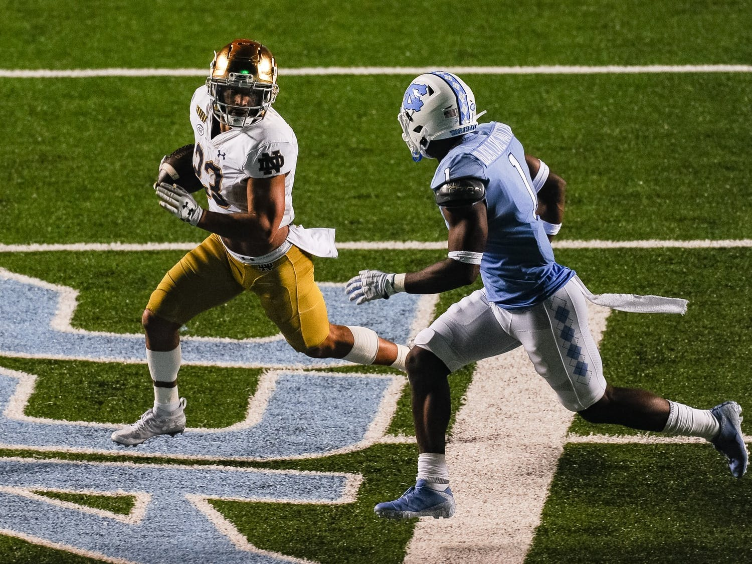 Notre Dame's sophomore running back Kyren Williams (23) runs downfield past UNC's  sophomore corner back Kyler McMichael (1) during a game in Kenan Memorial Stadium on Friday, Nov. 27, 2020. Notre Dame beat UNC 31-17.
