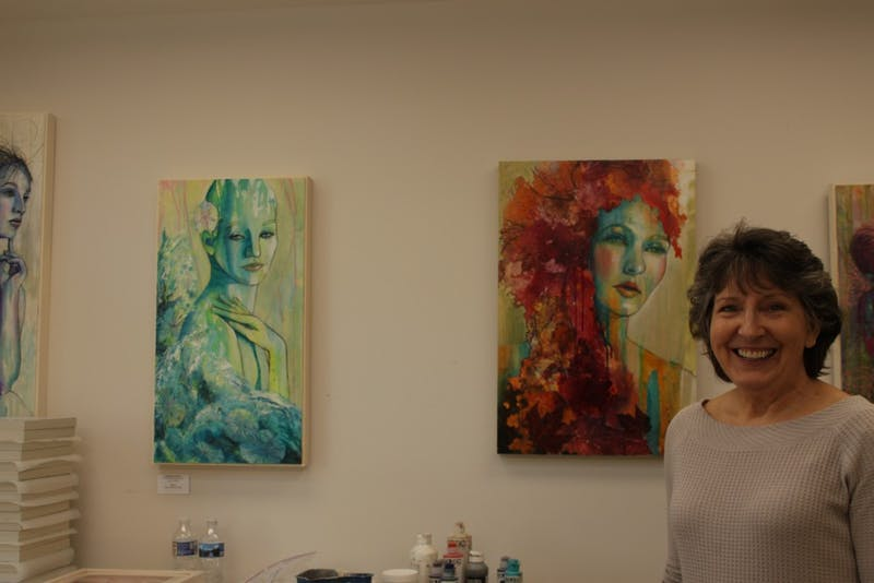 Visual artist Nancy Smith stands by her paintings in her home studio on Saturday, March 2, 2019. Nancy's paintings, which are mostly acrylic and mixed media, are being hosted by the FRANK gallery.
