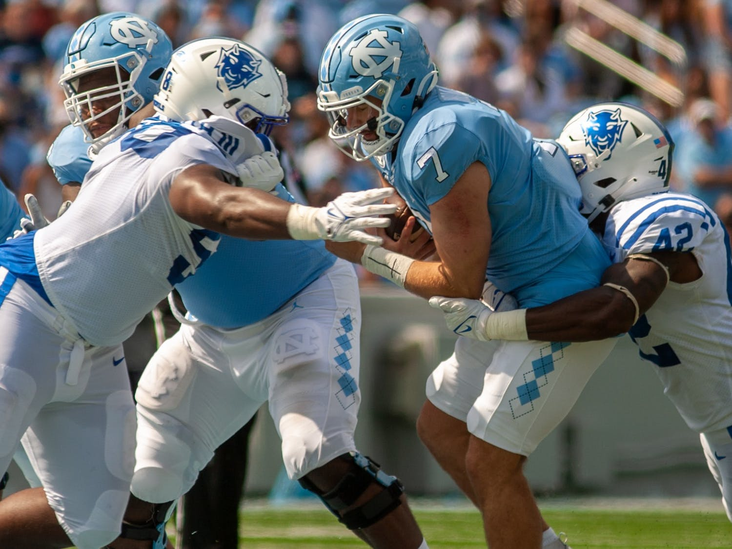 Junior quarterback Sam Howell (7) is tackled during a carry at the game against Duke on Oct. 2 at Kenan Stadium.