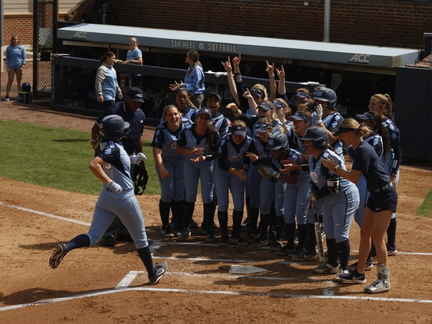 Sophomore catcher and first baseman Megan Dray is welcomed by her team into home plate during UNC's double header against the University of Virginia. The Tar Heels won both games 8-0 at the G. Anderson Softball Stadium on Sunday, Apr. 7, 2019.