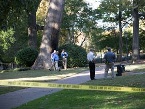 Police investigate an explosion at the Davie Poplar tree in McCorkle Place on Thursday afternoon.