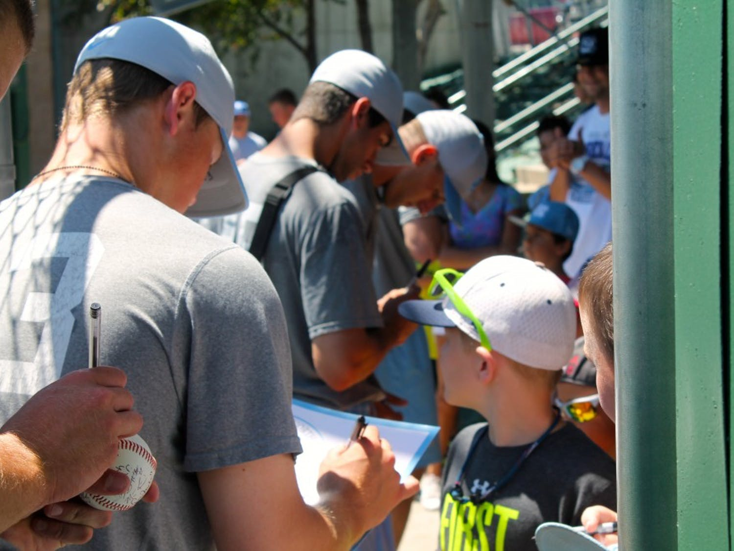 UNC's baseball team signs autographs for waiting fans on the way to the bus following Monday afternoon's practice.