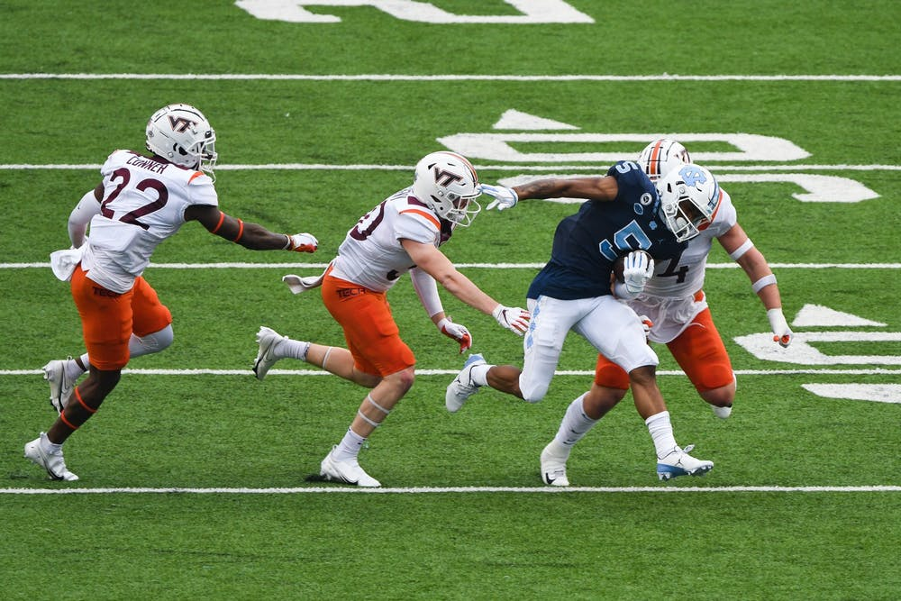 UNC senior wide reciever Dazz Newsome (5) attempts to run past members of Virginia Tech's defensive line during a game in Kenan Memorial Stadium on Saturday, Oct. 10, 2020. UNC beat Virginia Tech 56-45.