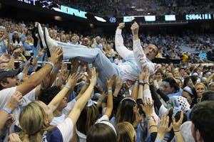 Clay Browning, a former graduate assistant coach for UNC football, crowd surfs in the bleacher level student section of the Dean Smith Center before the UNC men's basketball game vs. Duke on March 4, 2017.