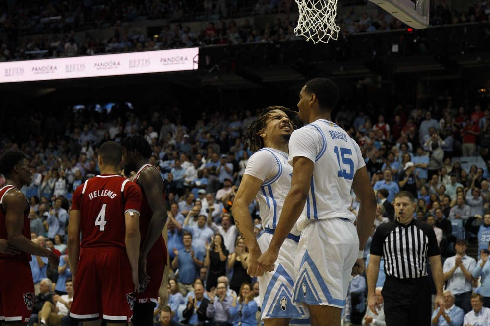 First-year guard Cole Anthony (2) and junior forward Garrison Brooks (15) celebrate after a dunk during the game against N.C. State during the game in the Smith Center on Tuesday, Feb, 25, 2020.  UNC beat N.C. State 85-79.
