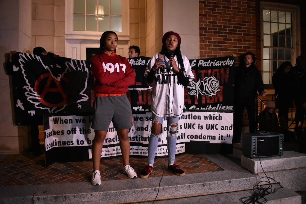 Qieara Lesesne (left), president of the Black Student Movement, stands firm as Vice President Alex Robinson (right) recites a poem during a protest against Chancellor Carol Folt and the Board of Trustees' proposal for Silent Sam's relocation in the Peace and Justice Plaza on Monday, Dec. 3, 2018.