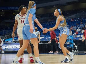 UNC graduate guard Stephanie Watts high-fives first-year forward Alyssa Utsby during Carolina's 80-71 first-round NCAA tournament loss at the Alamodome in San Antonio on March 22, 2021. Watts had a team-high 29 points in her final outing as a Tar Heel. Photo courtesy of Dana Gentry/UNC Athletics