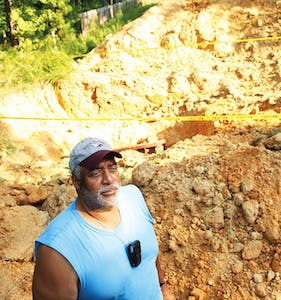David Caldwell stands in front ofthe hole that is being dug for a water pipeline in his backyard off Rogers Road.