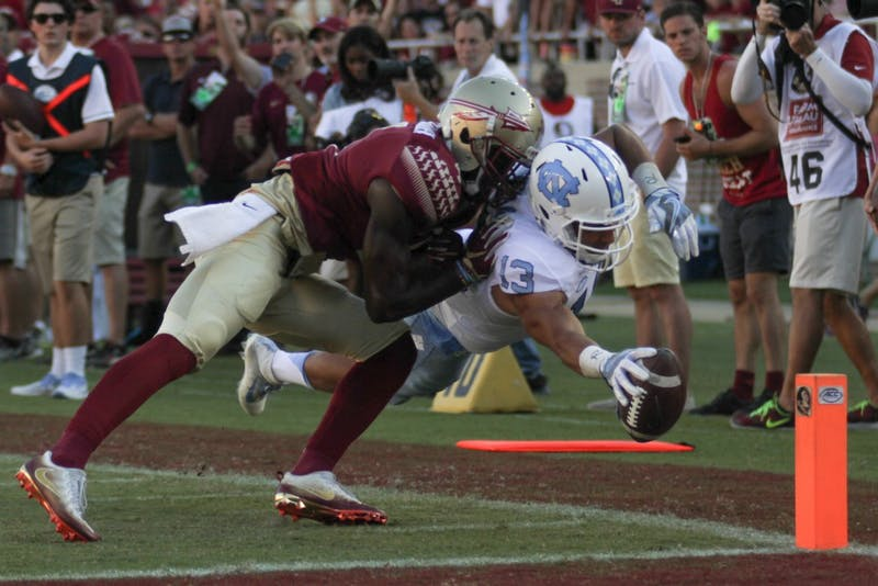 Mack Hollins (13) makes a diving play while being defended by an FSU player to score a touchdown.