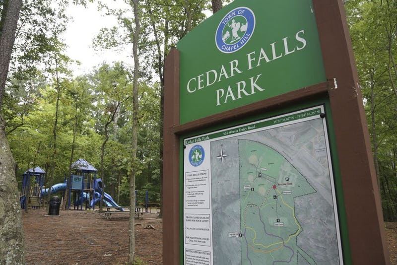 A sign sits on the side of a trail at Cedar Falls Park in Chapel Hill, and the old playground is in the background.