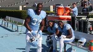 Running backs Elijah Hood (34), TJ Logan (8) and tailback Khris Francis (1) share a laugh on the sideline during the North Carolina football team's Spring Game on Saturday.