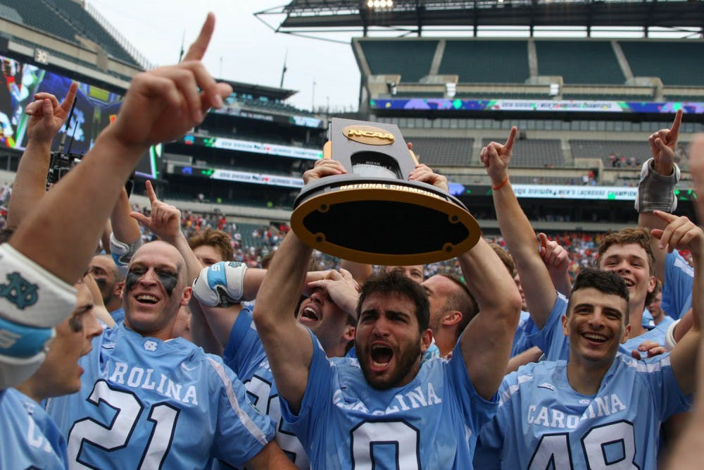 <p>UNC attacker Steve Pontrello (0) hoists up the NCAA national championship trophy while his teammates celebrate around him.&nbsp;The unseeded North Carolina men's lacrosse team defeated No. 1 Maryland 14-13 in overtime to claim the program's first national championship since 1991 on Monday at Lincoln Financial Field in Philadelphia.</p>