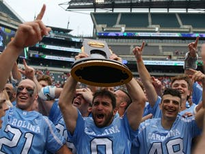 UNC attacker Steve Pontrello (0) hoists up the NCAA national championship trophy while his teammates celebrate around him.The unseeded North Carolina men's lacrosse team defeated No. 1 Maryland 14-13 in overtime to claim the program's first national championship since 1991 on Monday at Lincoln Financial Field in Philadelphia.