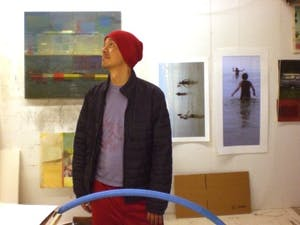 Former UNC associate professor Kimowan Metchewais looking at his work from within his studio. Metchewais is the featured artist of LIGHT: Art and Design's gallery on display in the Greenbridge building.