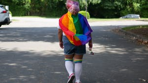 DTH Photo Illustration. A person walks down a street wearing a pride flag.