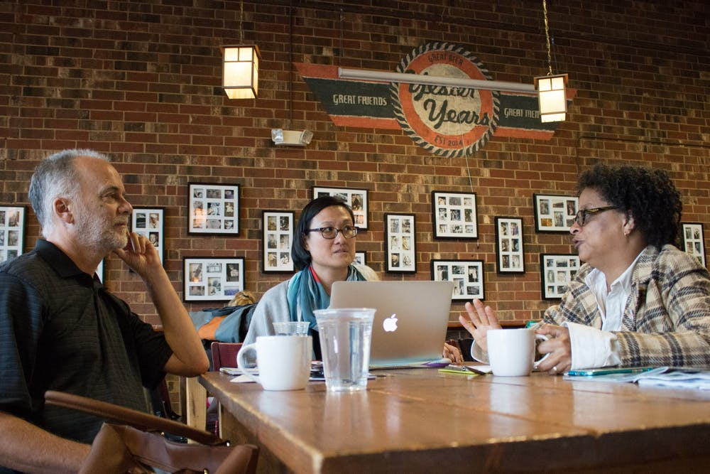 """<p>(From left) Frank Baumgartner, Jennifer Ho and Sharon Holland discuss their collaborative """"Intersectionality: Race, Gender, Sexuality and Social Justice"""" course at the Gray Squirrel coffee shop in Carrboro in 2016. Photo courtesy of Kristen Chavez, UNC College of Arts &amp; Sciences.</p>"""