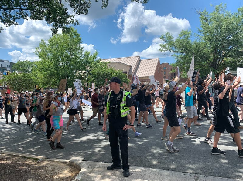 Protestors march past a Police Officer in Chapel Hill on Friday, June 12, 2020 during a protest against police brutality.