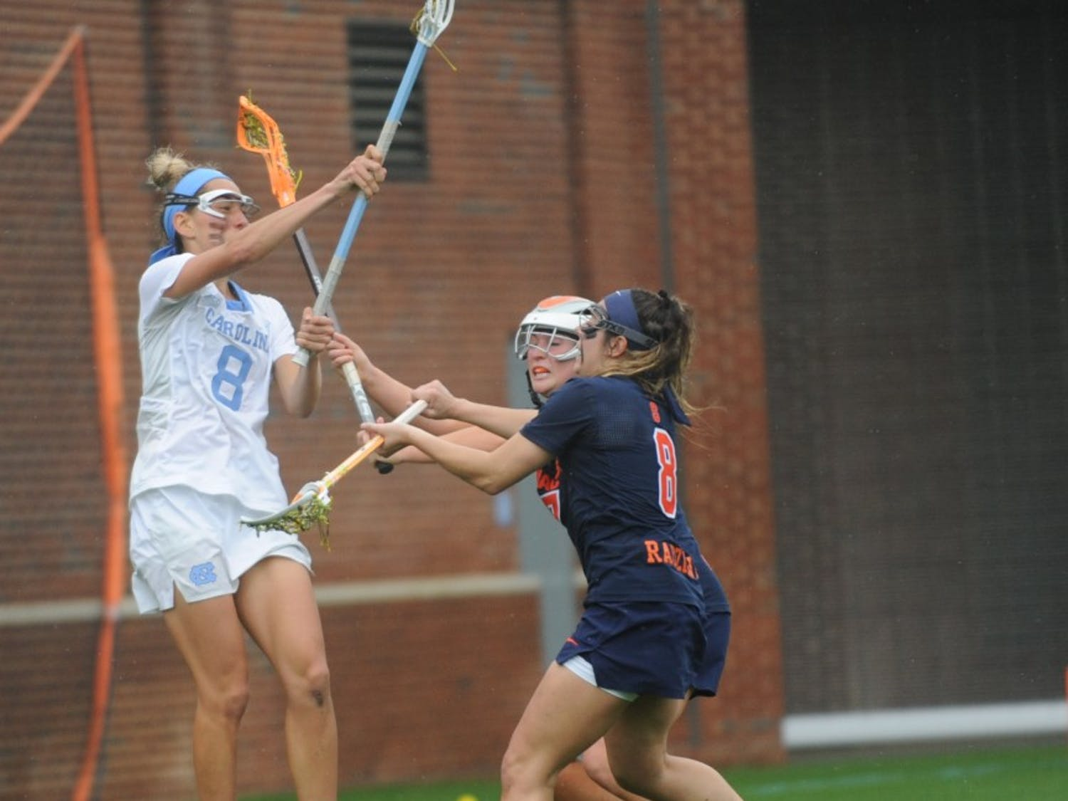 Women's lacrosse junior Katie Hoeg throws the ball over defenders during a game against Syracuse on April 13, 2019. UNC beat Syracuse 11-5.