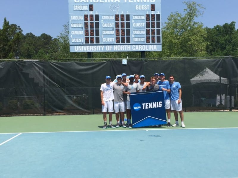 The UNC men's tennis team poses in front of their banner after beating Tennesee on May 13 to move on to the NCAA Sweet 16.