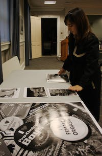 """Lisa Garland, a senior sociology major, sets up her  display at the """"We H(art) UNC"""" exhibition in Wilson Library. DTH/Daixi Xu"""