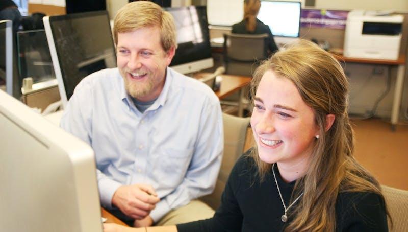Eliza Kern, senior political science major, in the Reese News digital newsroom with John Clark.