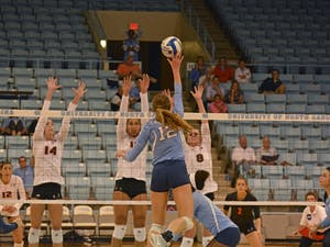 UNC Freshman Julia Scoles (12) spikes the ball against Miami players during the Tar Heels' 3-0 victory over UNC on Sunday, October 9.