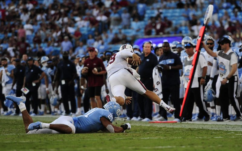 Junior linebacker Chazz Surratt (21) tackles USC's quarterback during the Belk College Kick Off in Charlotte, NC on Saturday, August 31, 2019.