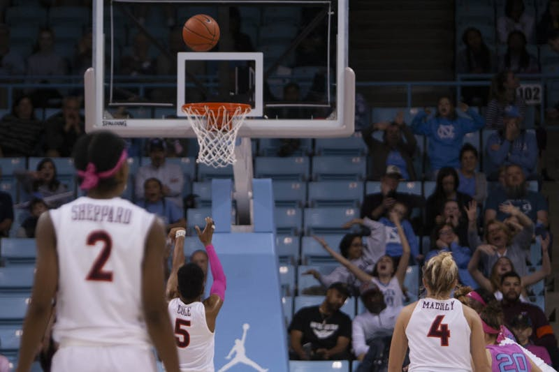 UNC fans scream and excitedly wave their arms in an attempt to distract Virginia Tech's Taja Cole (5) as she shoots the ball on Sunday, Feb. 9, 2020 at the Carmichael Arena. Carolina lost to Virginia Tech 72-63.