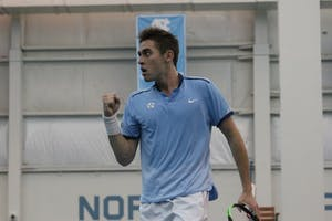 UNC's Benjamin Sigouin pumps his fist in celebration against Texas Christian on Feb. 5 in the Cone-Kenfield Tennis Center.