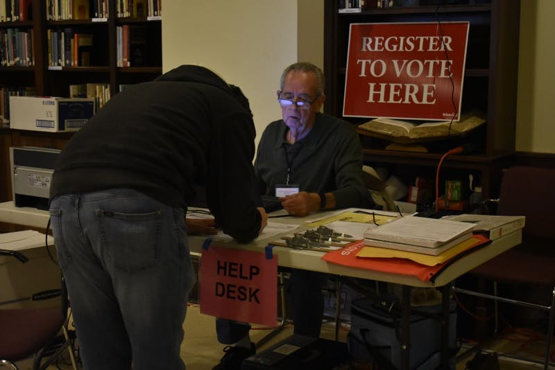 Precinct Chief Judge James Weathers volunteers at the Chapel of the Cross church at 304 E. Franklin St. on Oct. 23, 2018 helping voters register. The Chapel of the Cross severs as an early voter location close to the University of North Carolina at Chapel Hill's campus.