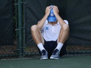 Sophomore Robert Kelly sits in isolation after losing 7-5 in a vital tiebreaker in the third set of his singles match. The UNC men's tennis team lost 4-3 to the University of Virginia in the AC semi-finals on Saturday.
