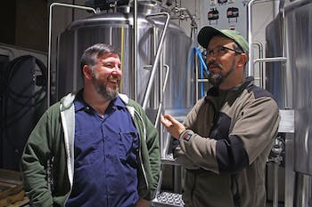 Erik Myers (left), founder of Mystery Brewing, and Keil Jansen, brewmaster of Ponysaurus Brewing Company, are joining with breweries to make a new beer.