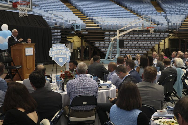 Coach Roy Williams gives some opening comments while attendants at the breakfast get served their food for the morning.