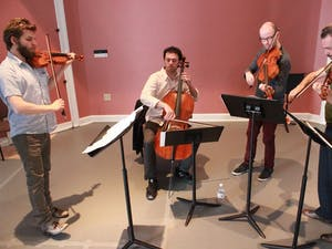 """Brooklyn Rider Quartet, pictured Thursday rehearsing at Gerrard Hall, performs on Sunday at Memorial Hall. Members (left to right) Johnny Gandelsman, Eric Jacobsen, Nicholas Cards, and Colin Jacobsen are glad to be back at Carolina for their tenth year; """"Music is more than notes on a page, it's life,"""" commented C. Jacobsen on music and its discussion within the university."""
