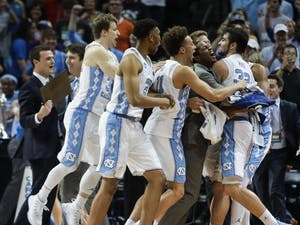 The UNC basketball team swarms Luke Maye (32) after winning  the NCAA Elite Eight game against Kentucky in Memphis on Sunday.