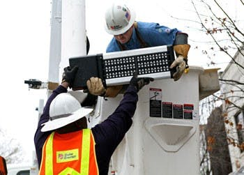 Duke Energy workers install one of 10 LED streetlights on Franklin Street in 2012 as part of a 12-month pilot program to evaluate the effectiveness of the LED lamps in increasing safety at night. The lamps are also expected to last longer and lower carbon emissions.