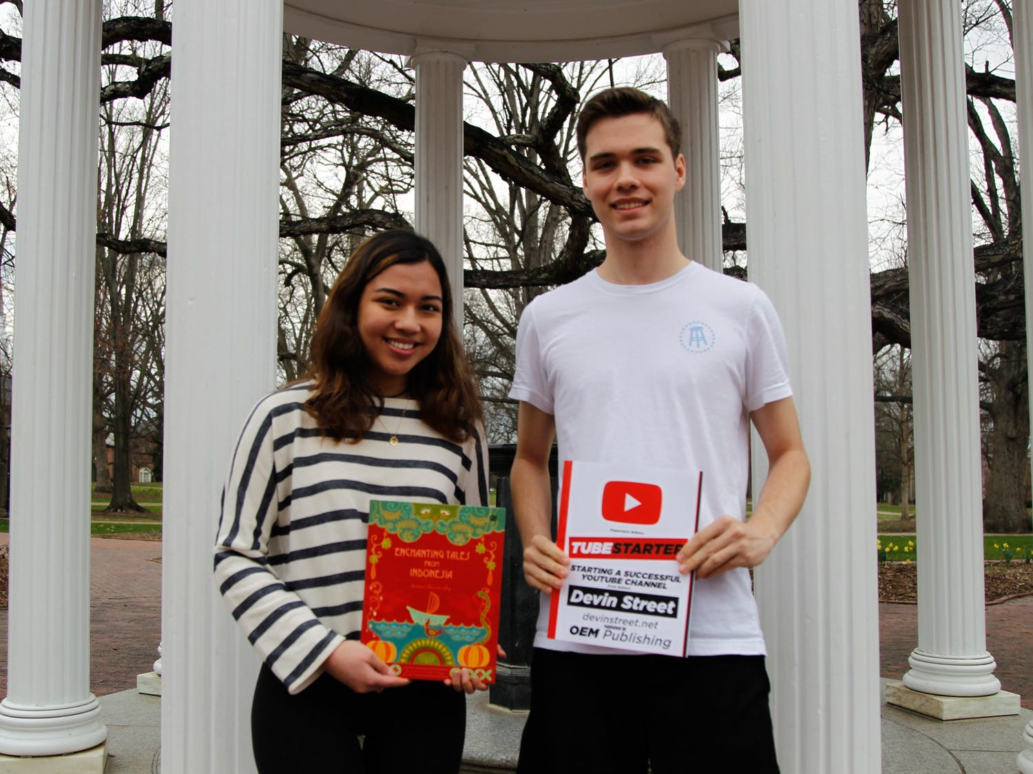 Devin Street, a first-year business major, poses for a portrait at the Old Well with his book, TubeStarter: Starting A Successful YouTube Channel, and Andari Deswandhy, a first-year global studies major, poses with her book, Enchanting Tales from Indonesia, on Feb. 26, 2020.
